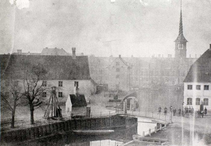 Gammelholm med en del af Ankersmedjen bag det lille vagthus og klokkestablen, til høje Holmen Kanal (nu overdækket) og Vagthuset (alt nu nedrevet) undtagen Børsen i baggrunden. Foto 1850'erne. Det Kongelige Bibliotek, Billedsamlingen.