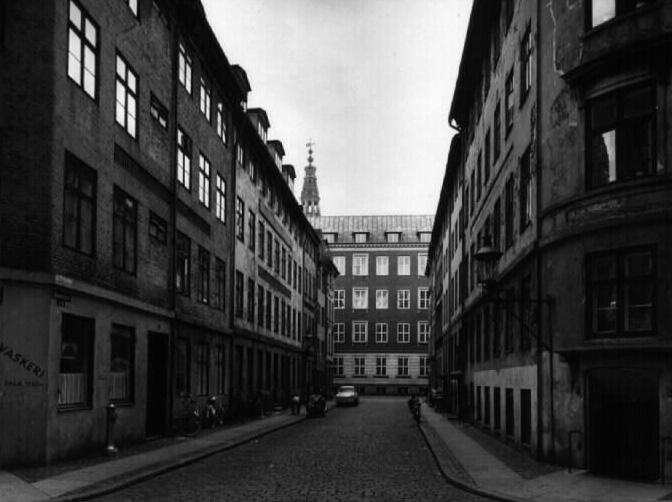 Hummergade kort før gaden blev nedlagt i 1950'erne set fra Nikolajgade mod Admiralgade med spiret fra Christiansborg i baggrunden. Huset til venstre næstyderst ved bilen var Bechs portbygning fra 1802. Det Kongelige Bibliotek, Billedsamlingen.