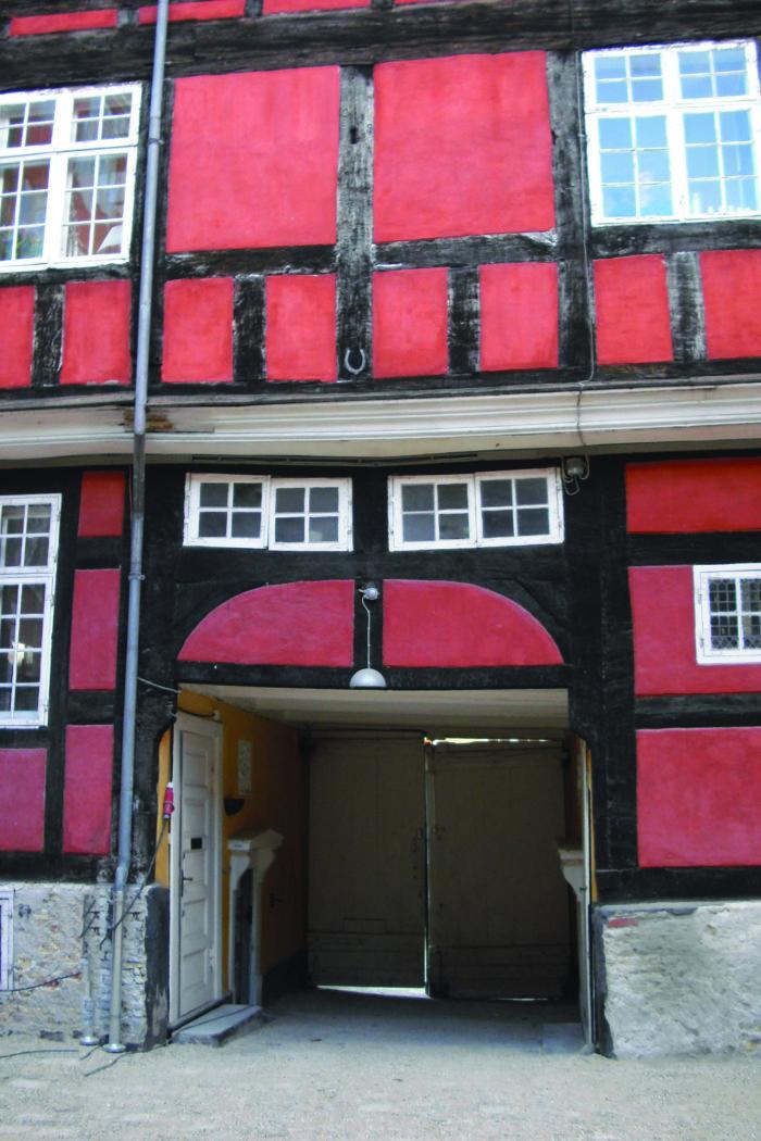 Bagsiden af forhuset, hvor der over porten og til højre for denne ses glasmalerier isat af ejeren glashandler Odin Hansens i 1920'erne. Foto Ida Haugsted 2017.
