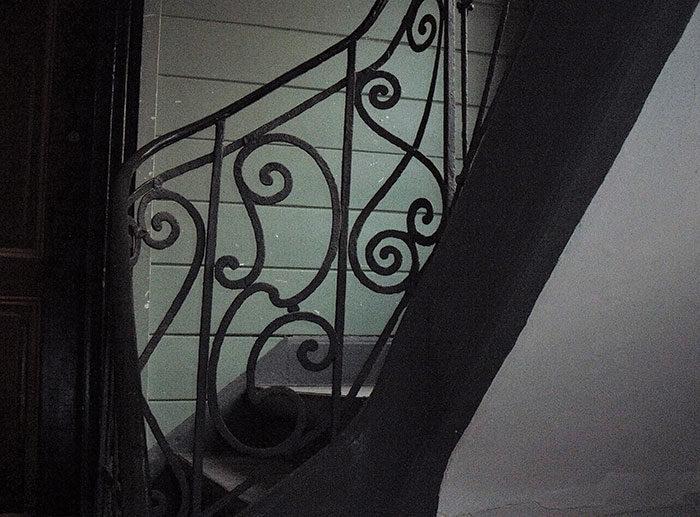 Jerngelænder i det vestlige trappehus fra begyndelsen af 1700-tallet med panelbeklædte vægge. Til venstre dør til stueetagen. Foto Ida Haugsted 2017.