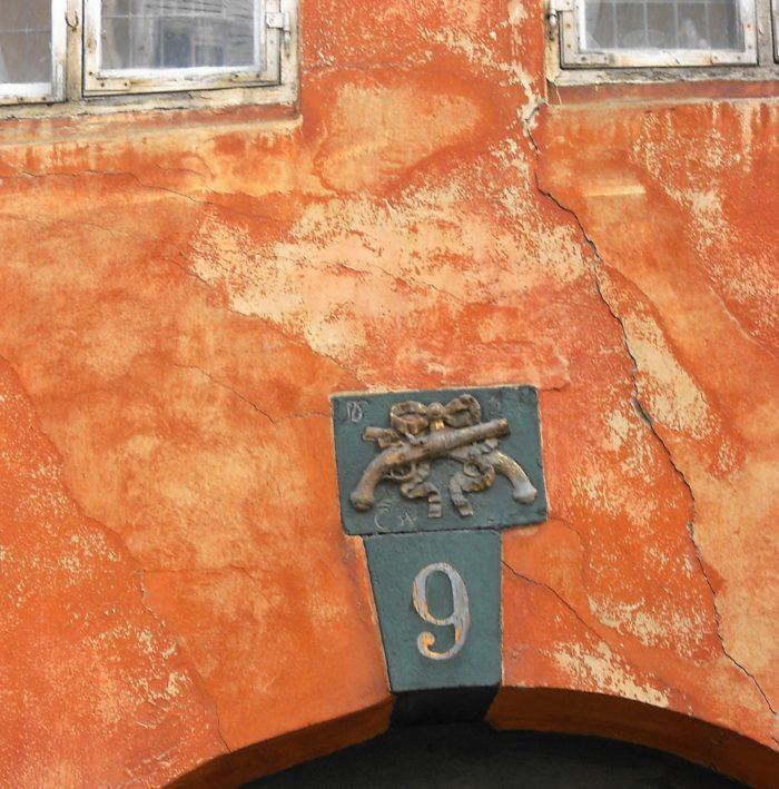 Slutsten over porten mod gaden med gadenummer 9 og ovenover to pistoler over kors med sløjfe. Nedenunder rester af indskrift: CW[K]. Foto Ida Haugsted 2017.